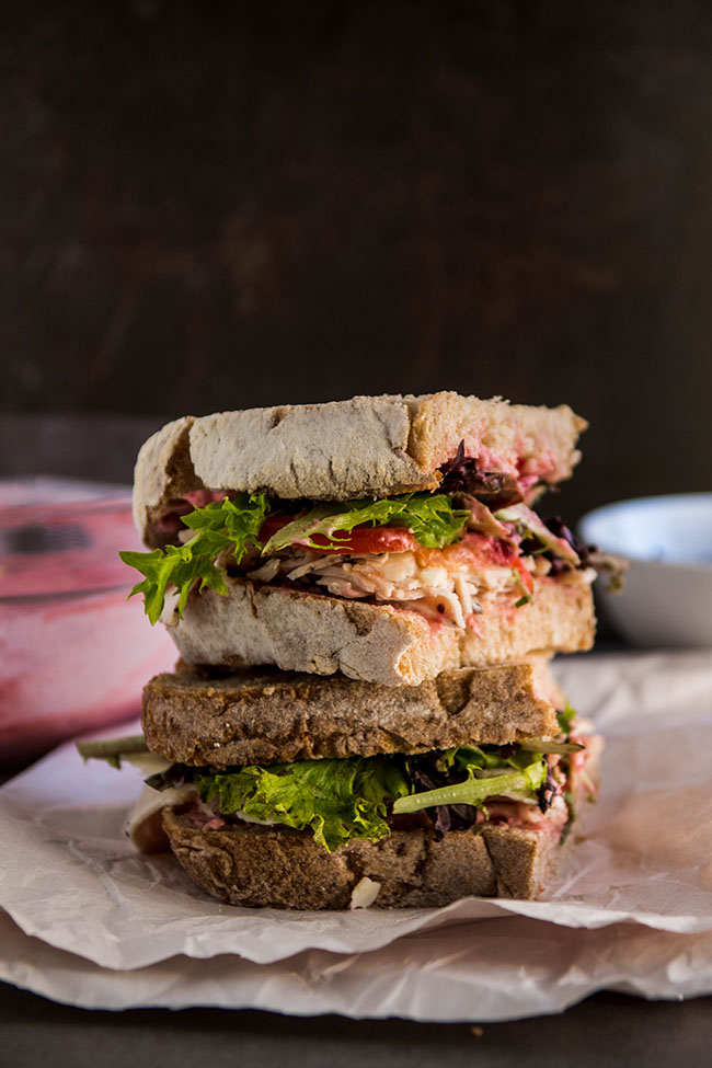 Two sandwich halves stacked on top of each other with a dark background and a bowl of cranberry mayonnaise.