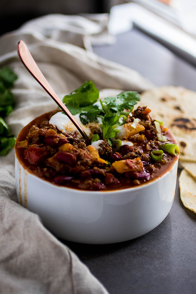 White bowl filled with chili and topped with cilantro, sour cream, and green onion with charred tortillas on the side and a copper spoon sticking out of the bowl