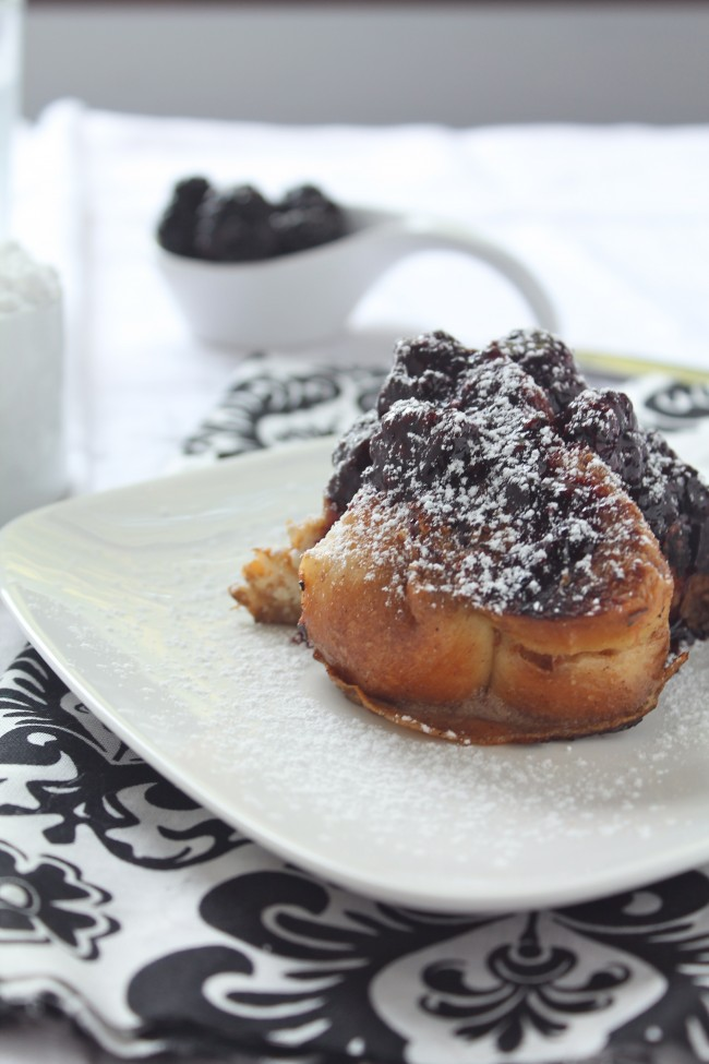 A piece of french toast on a white plate, topped with blackberry sauce and powdered sugar.
