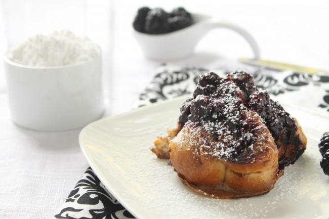 White plate filled with french toast and blackberry syrup, next to a dish full of powdered sugar.