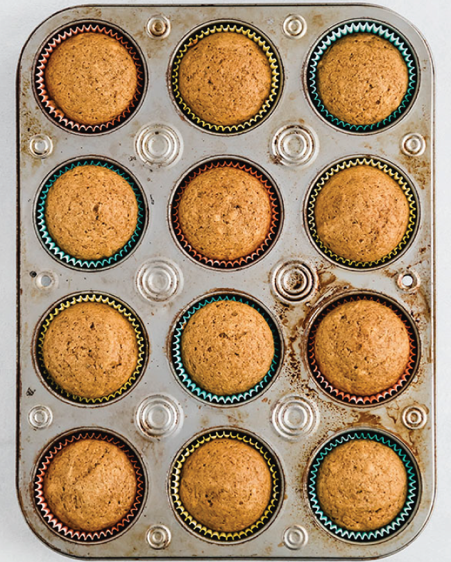 overhead photo of baked pumpkin cupcakes unfrosted in a muffin tin