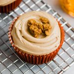pumpkin cupcake with maple frosting in a red liner sitting on a wire cooling rack