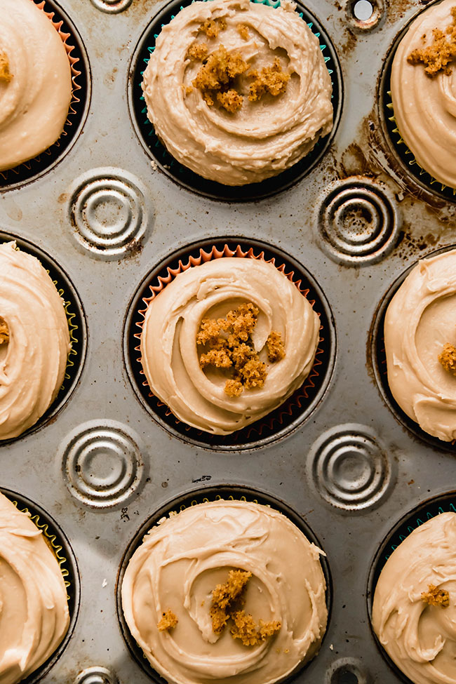 overhead photo of cupcakes in a muffin tin frosted with maple frosting