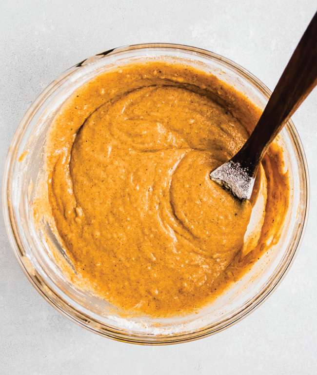 overhead photo of pumpkin cupcake batter in a glass bowl with a wooden spoon sticking out of it