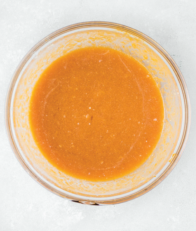 overhead photo of pumpkin batter mixture in glass bowl on a white background
