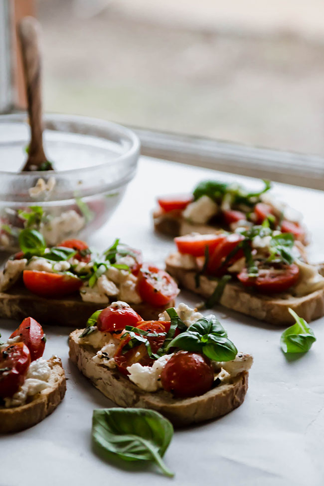 Four pieces of bruschetta toast next to a glass mixing bowl in front of a kitchen window