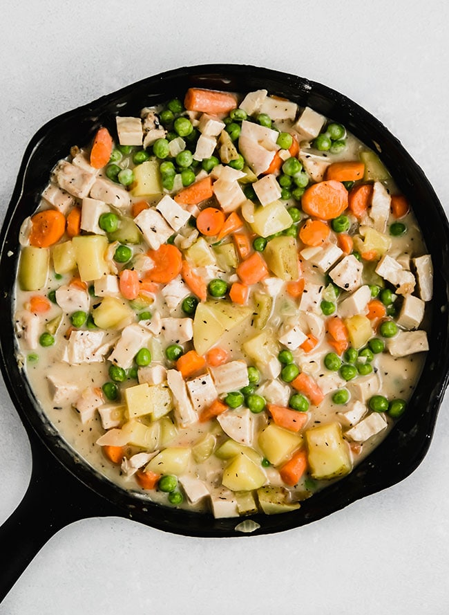 overhead photo of a cast iron skillet on a white table, filled with pot pie filling that includes carrots, peas, chicken, and potatoes