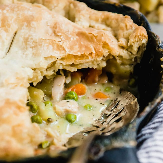 chicken pot pie in a cast iron skillet with a silver serving spoon