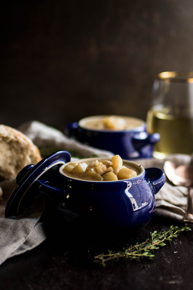 Two small blue bowls filled with potato soup on a dark background surrounded by a sprig of fresh thyme and a piece of bread
