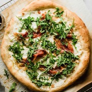 Overhead photo of white pizza topped with prosciutto, arugula, and mozzarella