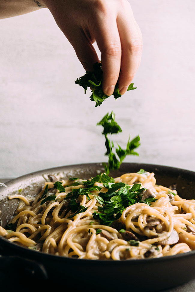 Side photograph of a hand in front of a white background dropping chopped parsley into a skillet full of spaghetti and mushrooms.