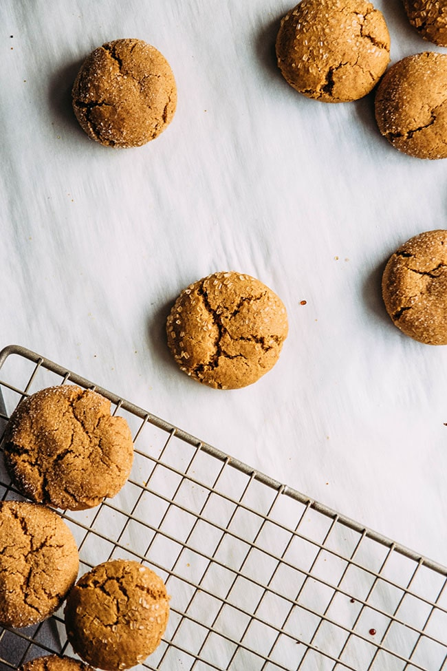 Overhead photo of small gingersnap cookies with a wire cooling rack in the lower left hand corner.