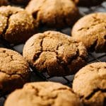 Side photo of gingersnap cookies grouped close together on a wire cooling rack.