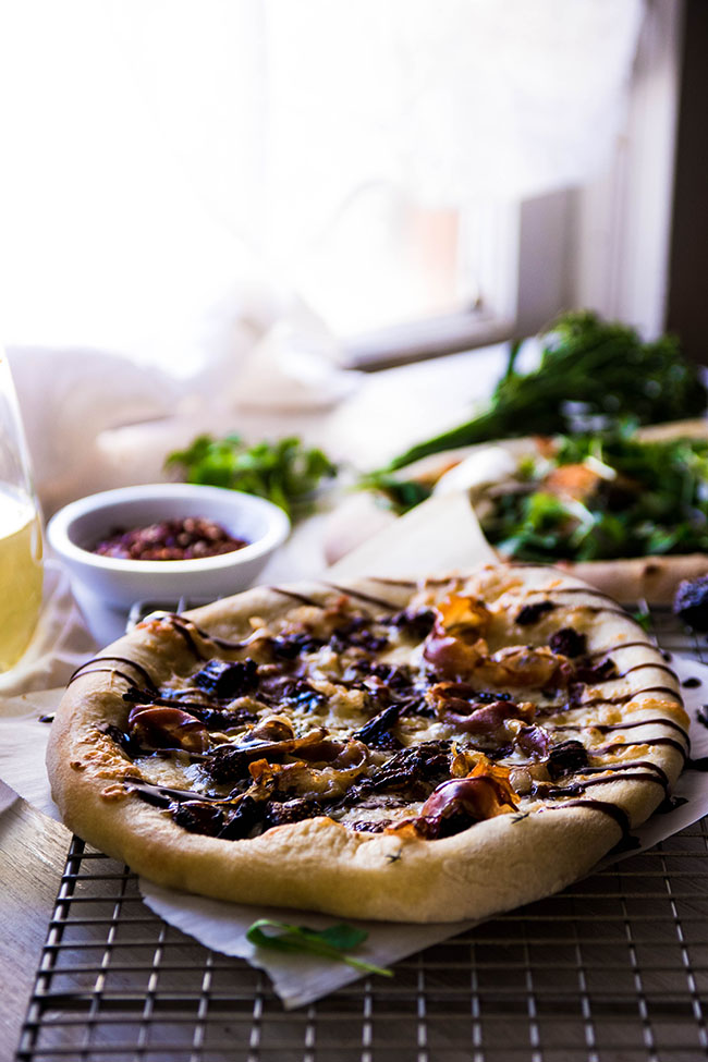 Side photograph of a small pizza with prosciutto and balsamic drizzle on a cooling rack in front of various pizza ingredients in small bowls.