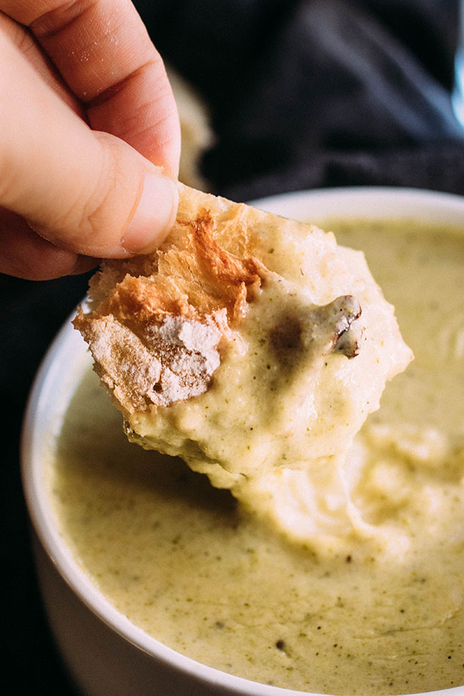 Hand dipping a small piece of bread into a bowl of cream of broccoli soup