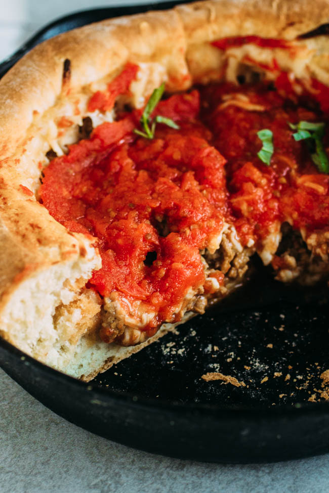Homemade deep dish pizza made in a cast iron skillet