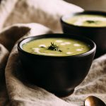 photo of green cream of leek and potato soup garnished with fresh thyme and cream in a small black bowl atop a brown linen napkin with a second bowl of soup in the background