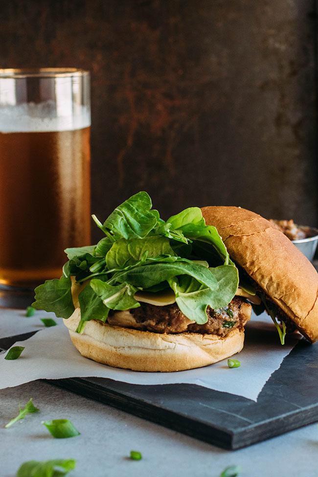 Side photograph of cheeseburger with arugula and an off-center top bun with a dark background.