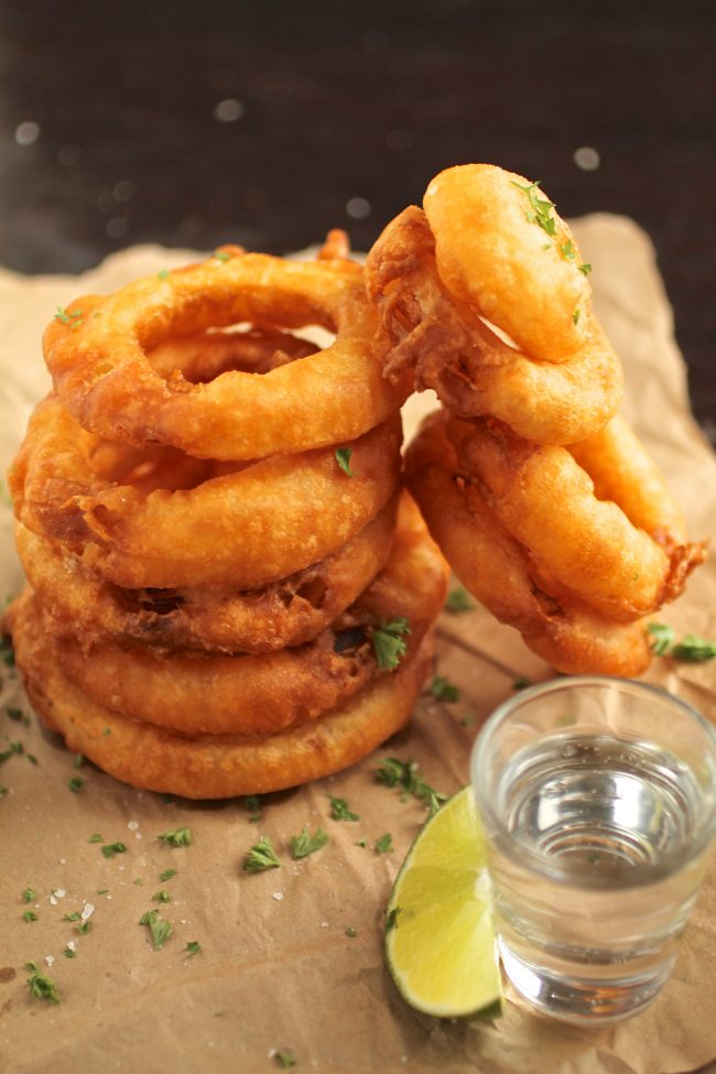 Tequila Battered Onion Rings | These homemade onion rings have a rich tequila batter and are sure to be a hit! Add the honey lime yogurt dipping sauce and you've got a perfect pair.