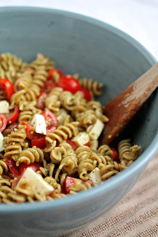 Kale and Basil Pesto Caprese Pasta Salad | This easy pasta salad is the perfect summertime recipe - a great side dish for your next potluck! Homemade kale pesto, some crispy prosciutto, fresh mozzarella and juicy tomatoes make for a simple pasta salad recipe that's sure to be a hit.