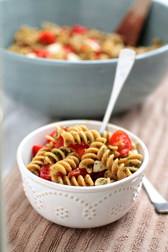 Kale and Basil Pesto Caprese Pasta Salad   This easy pasta salad is the perfect summertime recipe - a great side dish for your next potluck! Homemade kale pesto, some crispy prosciutto, fresh mozzarella and juicy tomatoes make for a simple pasta salad recipe that's sure to be a hit.