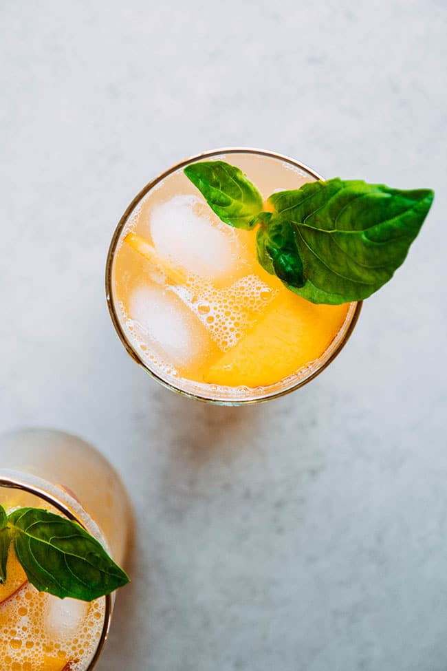 Overhead photo of bourbon cocktail with peaches, tonic water, and basil garnish.