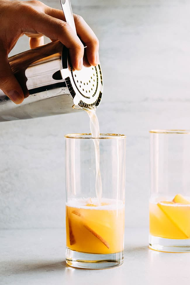 Hand holding a cocktail shaker pouring bourbon cocktail into a tall gold-rimmed glass in front of a white background.
