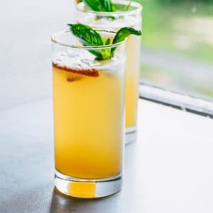 A peach bourbon cocktail in a tall glass by a window with basil garnish.