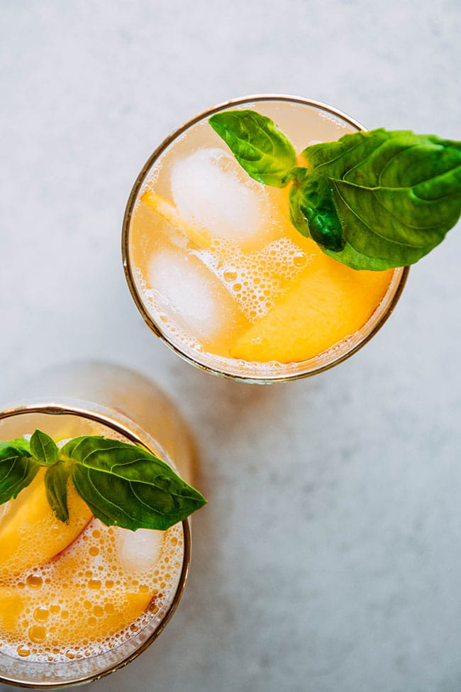 Peach bourbon spritzers. Peach cocktail in a gold-rimmed glass with sliced peaches and basil garnish.