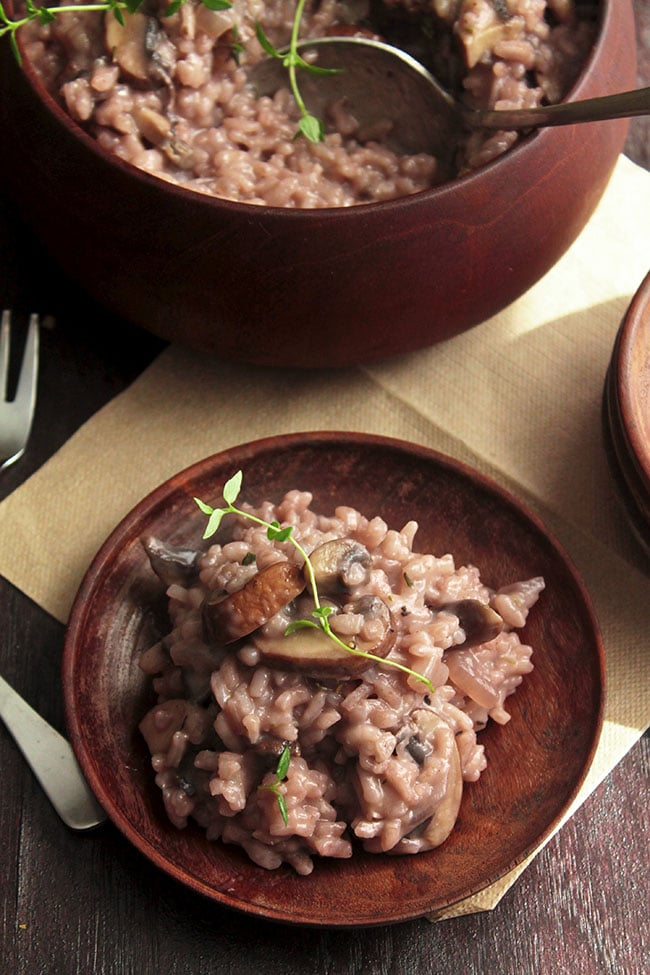 Overhead photo of red wine risotto with mushrooms and a fresh thyme garnish, sitting on a dark wooden plate with a brown background next to a brown bowl with more risotto.