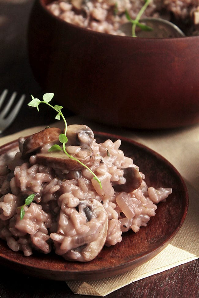 Pink risotto with mushrooms and fresh thyme on a dark wooden plate with a wooden bowl in the background.
