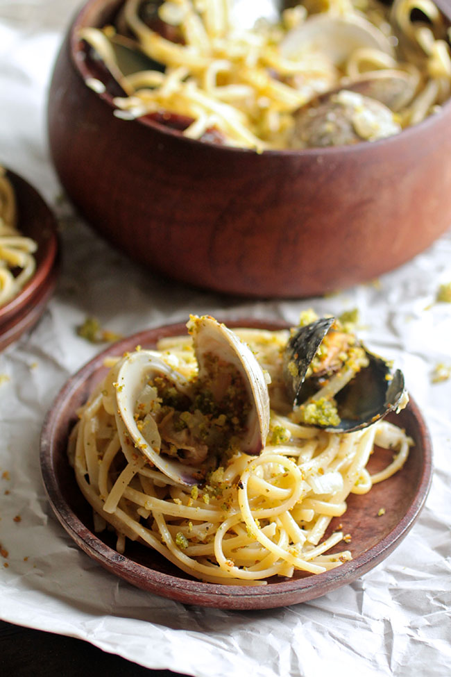 Shellfish Spaghetti with Pesto Toasted Bread Crumbs | This light and savory shellfish pasta recipe has a pesto white wine sauce, crispy pesto toasted breadcrumbs, and flavorful clams and mussels!