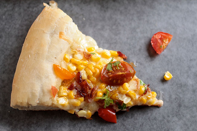 Corn and Tomato Pizza with Bacon and Gruyere | This easy homemade pizza gets a ton of flavor from crispy bacon, fresh summer corn and tomatoes, and shredded gruyere cheese.