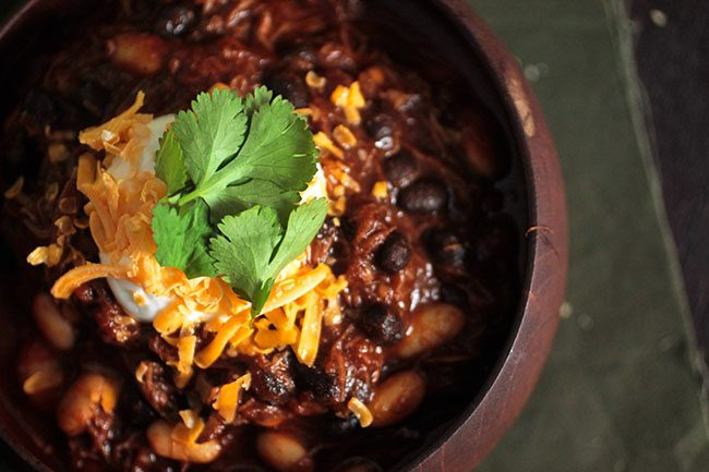 Beer Braised Short Rib Chili | This easy braised short rib chili recipe is packed with flavor and easy to make! Short ribs are braised in a tasty Guinness and tomato sauce that makes for a rich, comforting bowl of stew.