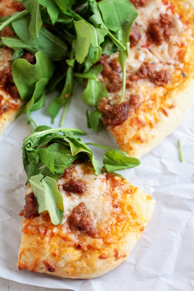 This easy homemade pizza recipe needs just a handful of ingredients - spicy Italian sausage, a quick tomato sauce, mozzarella cheese and a handful of crisp, fresh arugula.