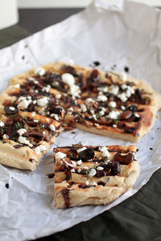 Grilled flatbread recipe with sautéed mushrooms, thyme, and goat cheese. Topped with a balsamic glaze. Vegetarian.