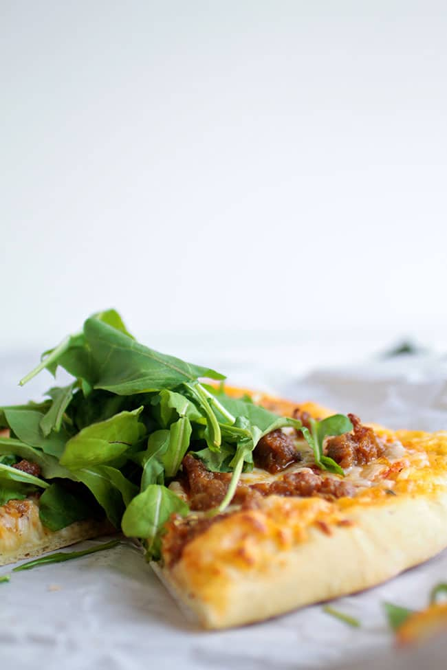 An easy pizza recipe in less time than it takes to wait for delivery. With spicy sausage, arugula, and an easy homemade pizza crust.