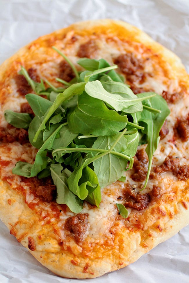Arugula Pizza with spicy sausage and crushed tomatoes