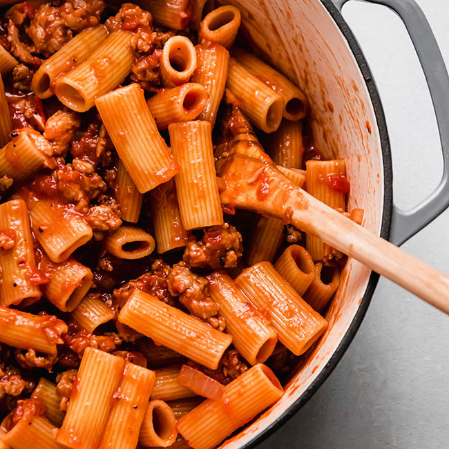 Wooden spoon stirring rigatoni and tomato sauce in a light grey pot.
