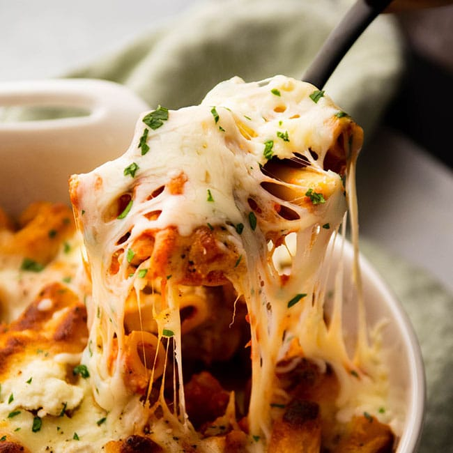 Spoon lifting baked ziti out of a white baking dish.