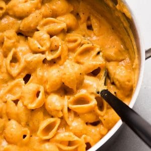 Black spoon stirring shell pasta with butternut squash sauce in a large pot.