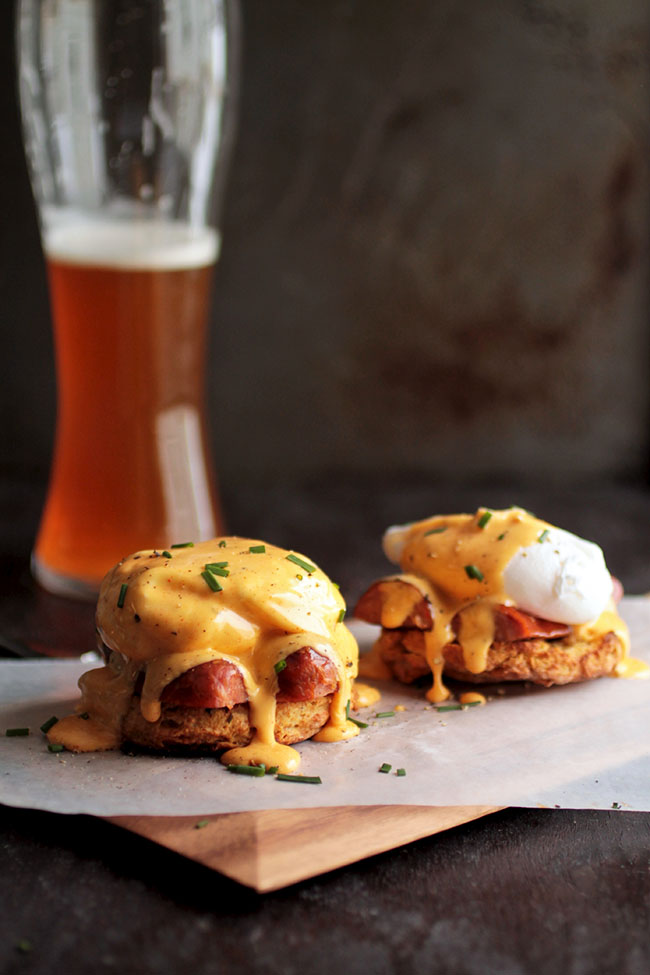 Cajun Eggs Benedict | Soft cheddar beer biscuits topped with spicy andouille sausage, poached eggs, and a spicy homemade hollandaise sauce.