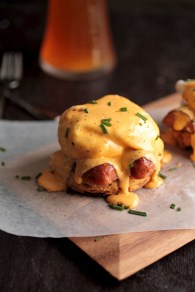 A cajun inspired eggs benedict recipe perfect for brunch! A spicy two-minute homemade hollandaise sauce, poached eggs, and andouille sausage on top of a cheddar beer biscuit.