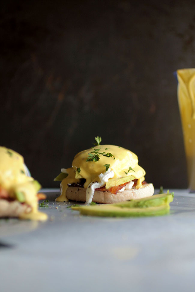 Avocado Eggs Benedict | Shake up your brunch routine with this easy eggs Benedict recipe and foolproof blender hollandaise sauce! Complete with fresh, creamy avocado, crispy bacon, and tangy goat cheese for a fun twist on this classic breakfast recipe.