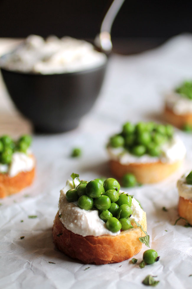 This tasty pea and mint crostini recipe is sure to be a hit! Topped with easy homemade garlic whipped feta cheese.