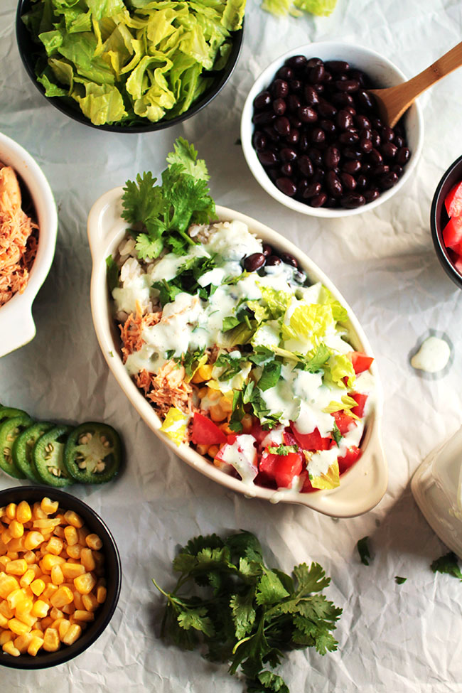 Plenty of veggies and an easy slow cooker salsa chicken makes this a delicious chicken burrito bowl recipe!