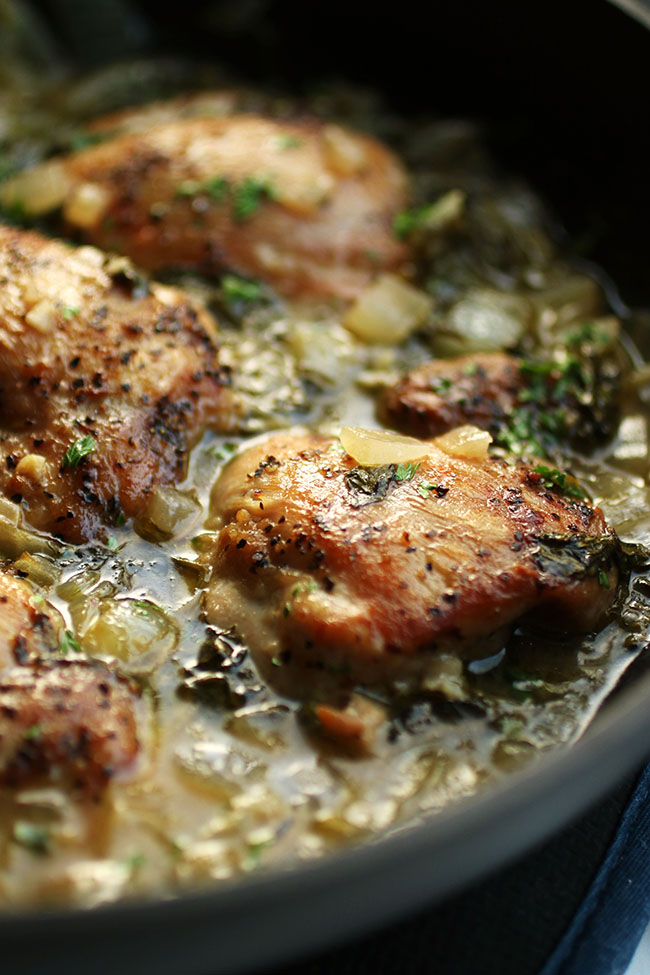 Baked chicken thighs in a pot with chicken stock, spinach, and chopped onions