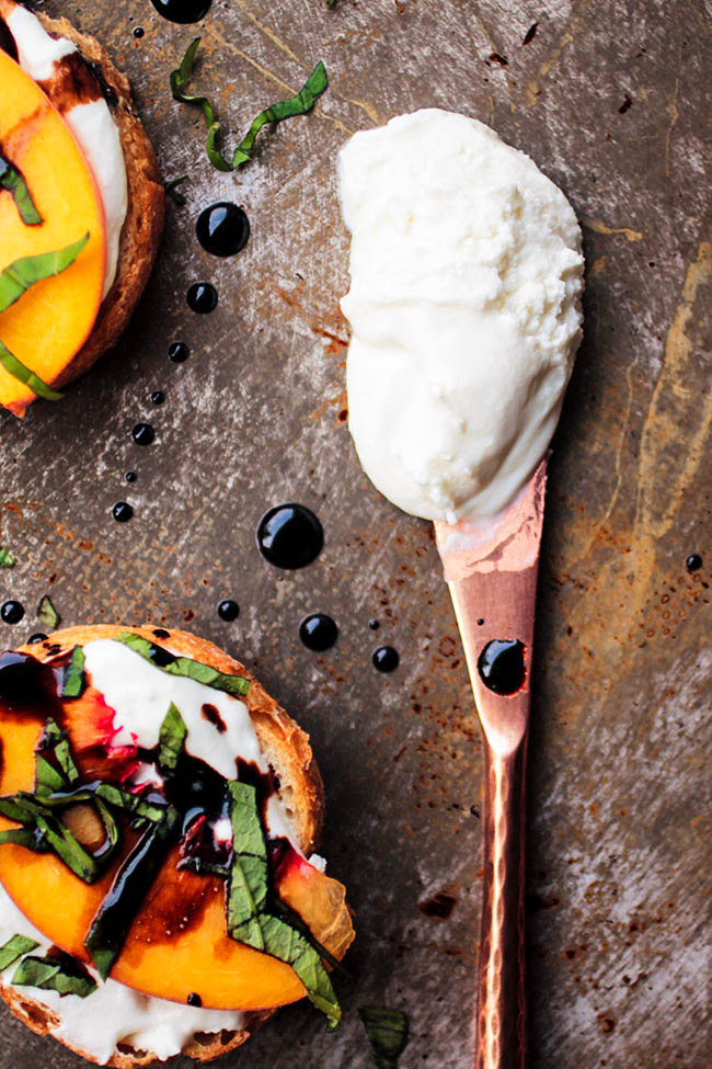 Summer bruschetta appetizer recipe with peaches, whipped goat cheese, and balsamic reduction. Vegetarian.