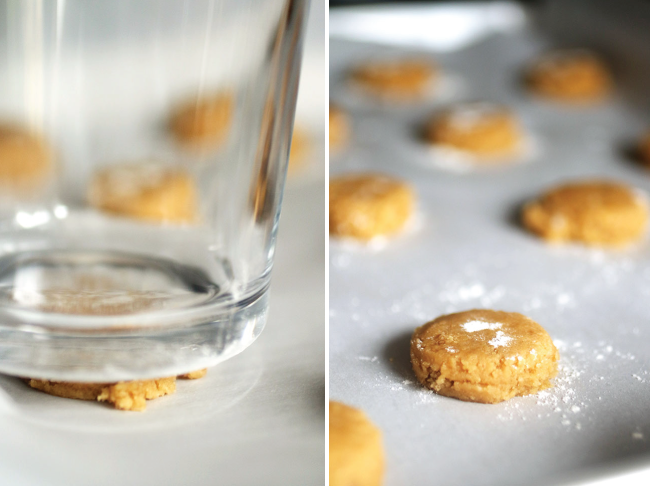 drinking glass pressing down on balls of peanut butter cookie dough