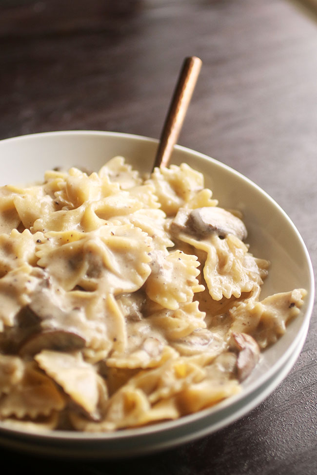 Bowtie pasta with parmesan sauce in a shallow white bowl on a dark brown background with a copper fork